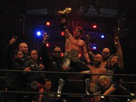 Ten members of the Bullet Club group celebrate in a professional wrestling ring. Several are using a hand gesture, extending the index and little finger, with the tips of the renaming fingers touching