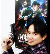 File:Yasuhiro Ampo poses with Biohazard 5 Poster.jpg
