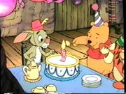 Pooh lighting a candlestick on the cake