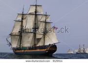 Stock-photo-vintage-frigate-sailing-ship-at-sea-under-full-sail-with-tall-ships-in-the-background-9129514