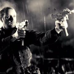 An IRA mercenary fires a pair of Micro Uzis at Dwight McCarthy (Clive Owen).