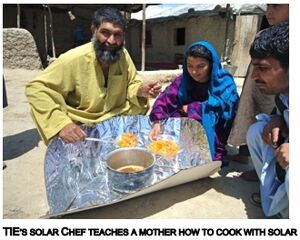 A workshop trainer from TIE teaches a mother how to use her new CooKit, 3-10-14