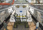 Technicians carefully position an Orion flight test crew module