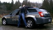 Dean tied to police car