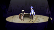 S3E34.179 Mordecai and Rigby Next to a Desk