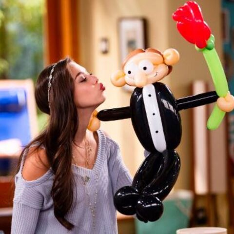 Phoebe kissing a balloon monkey.