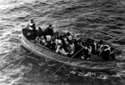 Photograph of a lifeboat, filled with people wearing life jackets, being rowed towards the camera.