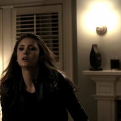 Katherine is fighting Stefan in living room 1, fireplace on her right, the side window behind her