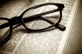 10298353-close-up-of-old-dictionary-and-black-glasses