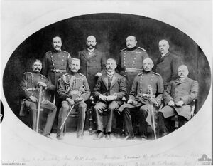 Formal group portrait of nine men, four sitting at the front and five standing behind. Three are wearing suits; the others are wearing formal double breasted military uniforms with sashes.