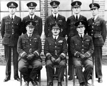 Portrait of eight men in dark military uniforms with peaked caps, five standing and three seated