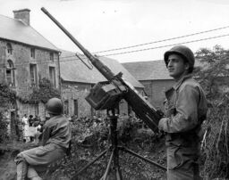 Group of French citizens gather outside a house under watch of an M2HB machine gun, Normandy 1944