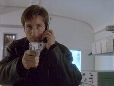 Fox Mulder aims a gun in 1997